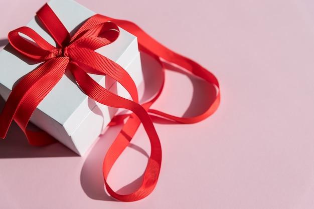 Witte geschenkdoos met rood lint en boog