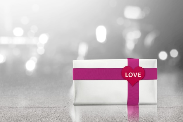 Witte geschenkdoos met rood lint en hartvorm met liefdetekst op de vloer met vage lichte achtergrond