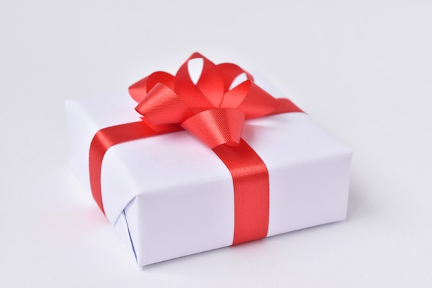 Witte geschenkdoos met rood lint op witte achtergrond