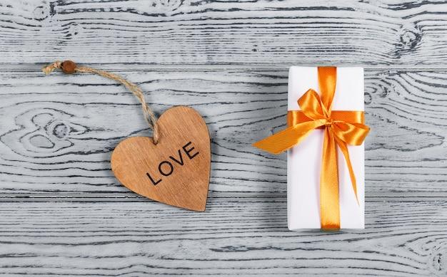 Witte geschenkdoos met strik en houten kaart in de vorm van hart