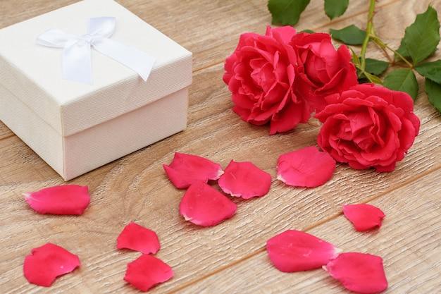Witte geschenkdoos, rozenblaadjes en mooie rozen op de houten achtergrond. concept van het geven van een geschenk op vakantie. bovenaanzicht.