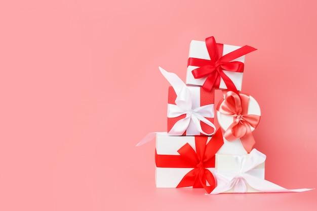 Witte geschenkdozen met rode satijnen linten op een roze achtergrond. feestelijke cadeaus voor valentijnsdag, internationale vrouwendag, bruiloft of verloving.