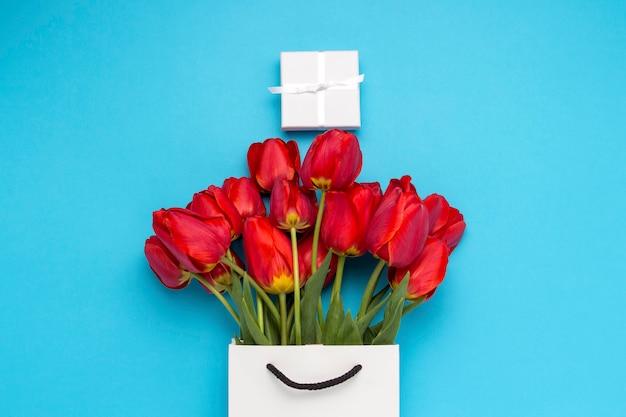 Witte geschenktas, een kleine witte geschenkdoos en een boeket rode tulpen op een blauwe. concept biedt een verloving of huwelijk, winkelen
