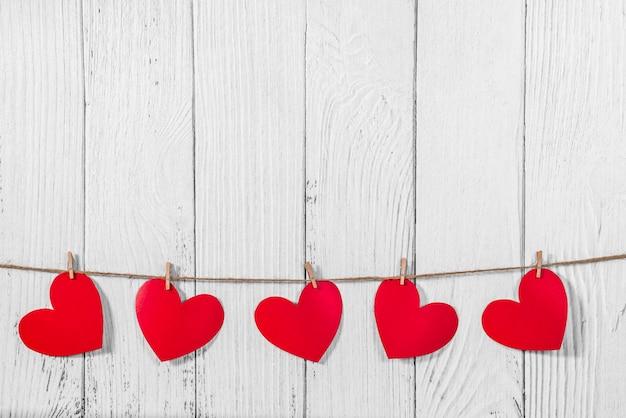Witte geschilderde houten achtergrond met een slinger van rode harten. natuurlijk touw en wasknijpers. concept van erkenning van liefde, romantische relaties, valentijnsdag in grungestijl. kopieer ruimte