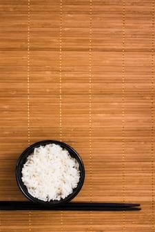 Witte gestoomde rijst in zwarte ceramische kom met eetstokjes