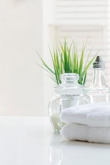 Witte gevouwen handdoeken en glazen fles op witte tafel met kopie ruimte.