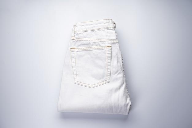 Witte gevouwen spijkerbroek, achterzak, platliggend.