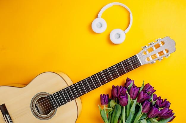 Witte gitaar en witte draadloze koptelefoon op de oranje achtergrond, lentebloemen, bos van paarse tulpen, witte gitaar en bloemen, lentemuziek poster.