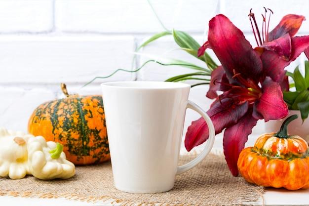 Witte grote koffie latte mok met pompoen en rode lelie
