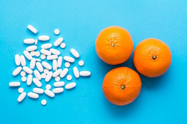 Witte grote ovale pillen en rijpe sinaasappelen op een blauwe achtergrond. medicijnen en synthetische vitamines. het concept van het kiezen van medicijnen en natuurlijk fruit. bovenaanzicht