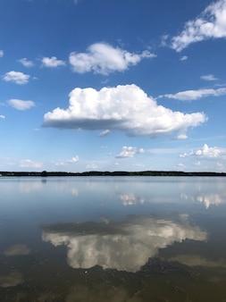 Witte grote pluizige wolk op een blauwe hemel weerspiegeld in een helder meerwater met een bos horizonlijn.