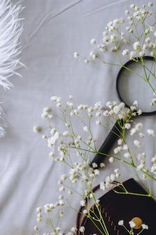 Witte gypsophila bloemen, een portemonnee voor munten en een vergrootglas op grijze stof