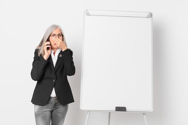 Witte haar zakenvrouw van middelbare leeftijd met een leeg bord kopieerruimte.