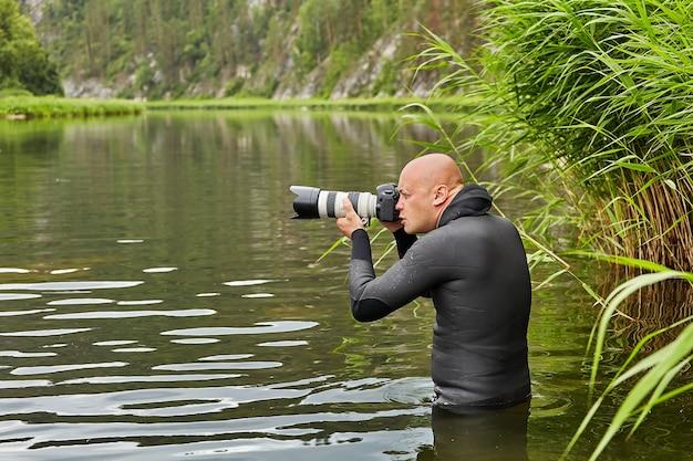 Witte haarloze man in waterdichte doek staat in de rivier met een digitale camera in zijn handen en neemt foto's van bos en rivier, ecotoerisme.