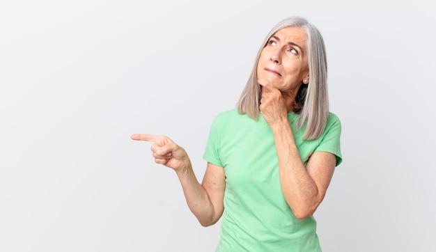 Witte haarvrouw van middelbare leeftijd denkt, voelt zich twijfelachtig en verward en wijst naar de zijkant