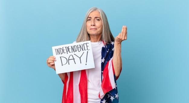Witte haarvrouw van middelbare leeftijd die capice of geldgebaar maakt en u zegt te betalen. onafhankelijkheidsdag concept