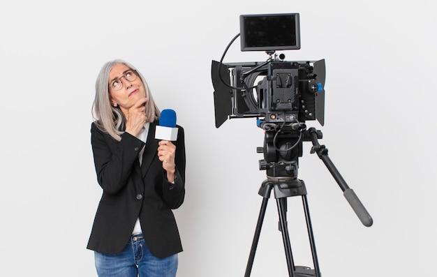 Witte haarvrouw van middelbare leeftijd die denkt, zich twijfelachtig en verward voelt en een microfoon vasthoudt. tv-presentator concept