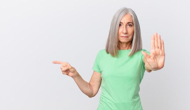 Witte haarvrouw van middelbare leeftijd die er serieus uitziet en een open handpalm laat zien die een stopgebaar maakt en naar de zijkant wijst