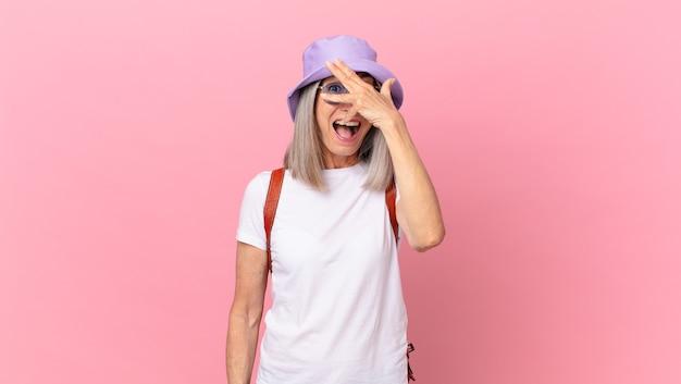 Witte haarvrouw van middelbare leeftijd die geschokt, bang of doodsbang kijkt en haar gezicht bedekt met de hand. zomer concept
