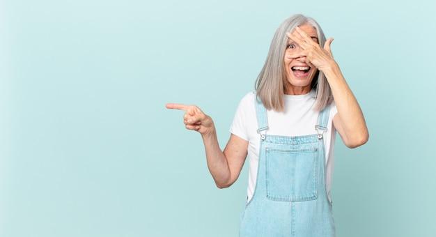 Witte haarvrouw van middelbare leeftijd die geschokt, bang of doodsbang kijkt, haar gezicht bedekt met de hand en naar de zijkant wijst