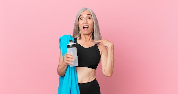 Witte haarvrouw van middelbare leeftijd die geschokt en verrast kijkt met wijd open mond, wijzend naar zichzelf met een handdoek en een waterfles. fitnessconcept