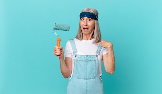 Witte haarvrouw van middelbare leeftijd die geschokt en verrast kijkt met wijd open mond, wijzend naar zichzelf met een roller die een muur schildert