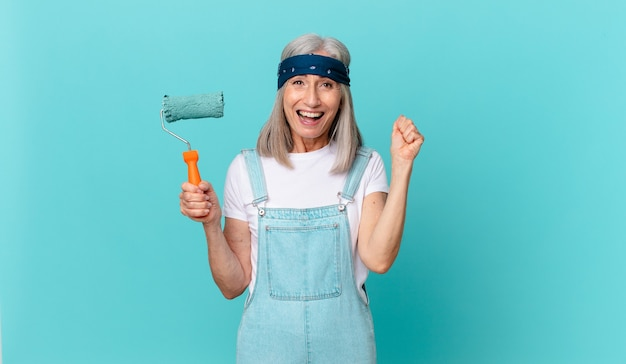 Witte haarvrouw van middelbare leeftijd die geschokt is, lacht en succes viert met een roller die een muur schildert