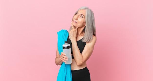 Witte haarvrouw van middelbare leeftijd die lacht met een gelukkige, zelfverzekerde uitdrukking met de hand op de kin met een handdoek en een waterfles. fitnessconcept