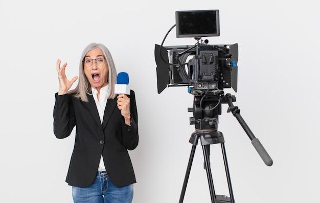 Witte haarvrouw van middelbare leeftijd die met handen in de lucht schreeuwt en een microfoon vasthoudt. tv-presentator concept