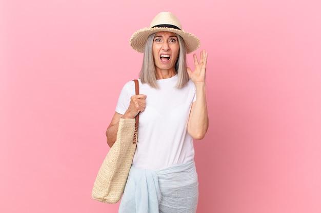 Witte haarvrouw van middelbare leeftijd die met handen omhoog in de lucht schreeuwt. zomer concept