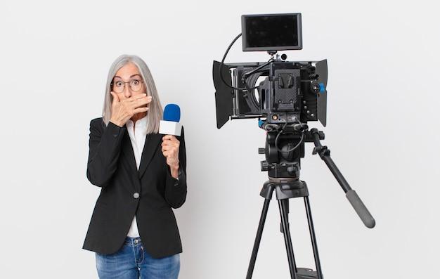 Witte haarvrouw van middelbare leeftijd die mond bedekt met handen met een geschokte en een microfoon vasthoudt. tv-presentator concept