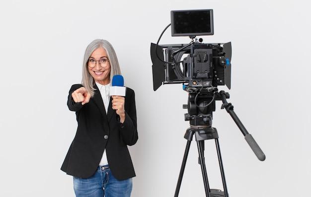 Witte haarvrouw van middelbare leeftijd die naar de camera wijst en jou kiest en een microfoon vasthoudt. tv-presentator concept