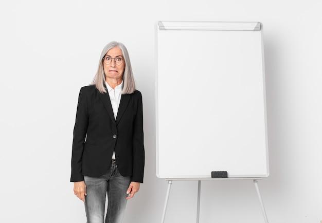 Witte haarvrouw van middelbare leeftijd die verbaasd en verward kijkt en een bord kopieerruimte. bedrijfsconcept