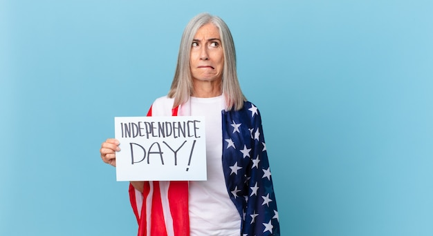Witte haarvrouw van middelbare leeftijd die verbaasd en verward kijkt. onafhankelijkheidsdag concept