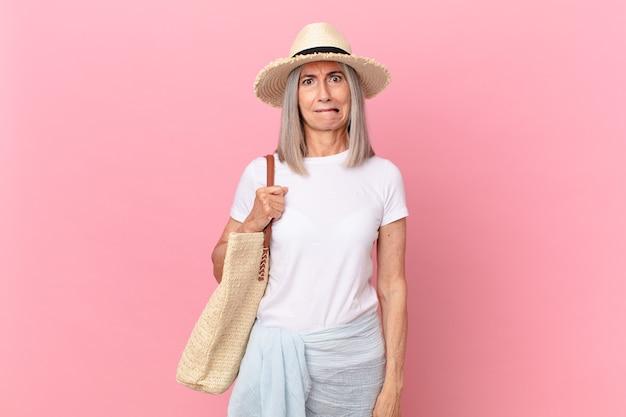 Witte haarvrouw van middelbare leeftijd die verbaasd en verward kijkt. zomer concept