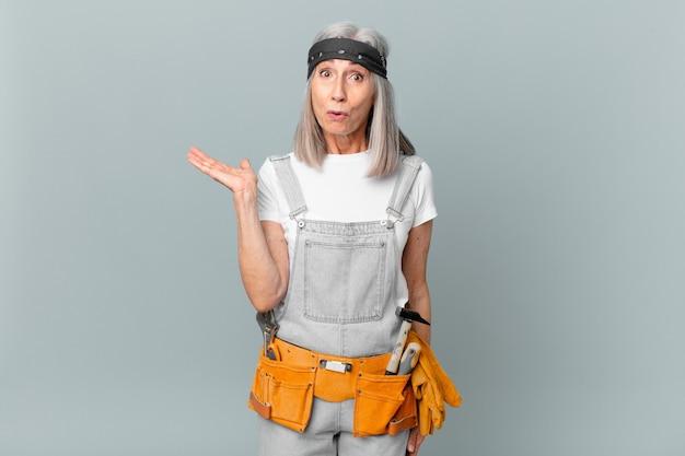Witte haarvrouw van middelbare leeftijd die verrast en geschokt kijkt, met open mond terwijl ze een object vasthoudt en werkkleding en gereedschap draagt. huishoudconcept