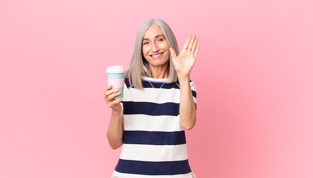 Witte haarvrouw van middelbare leeftijd die vrolijk lacht, met de hand zwaait, je verwelkomt en begroet en een afhaalkoffiecontainer vasthoudt