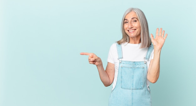 Witte haarvrouw van middelbare leeftijd die vrolijk lacht, met de hand zwaait, je verwelkomt en begroet en naar de zijkant wijst