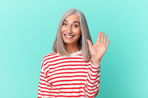 Witte haarvrouw van middelbare leeftijd die vrolijk lacht, met de hand zwaait, je verwelkomt en begroet
