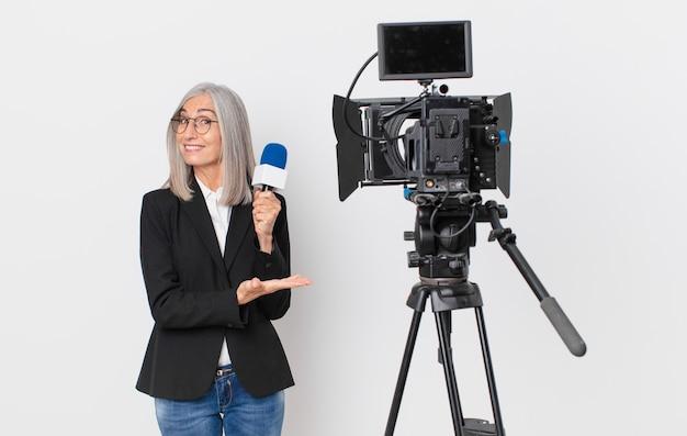 Witte haarvrouw van middelbare leeftijd die vrolijk lacht, zich gelukkig voelt en een concept toont en een microfoon vasthoudt. tv-presentator concept