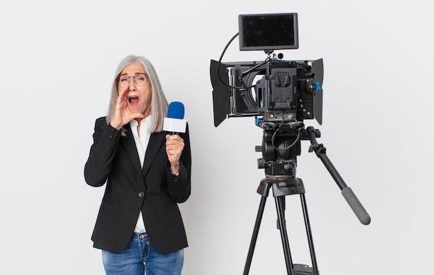 Witte haarvrouw van middelbare leeftijd die zich gelukkig voelt, een grote schreeuw geeft met de handen naast de mond en een microfoon vasthoudt. tv-presentator concept