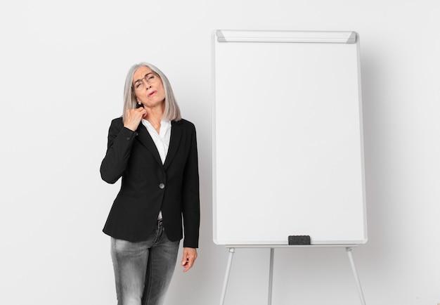 Witte haarvrouw van middelbare leeftijd die zich gestrest, angstig, moe en gefrustreerd voelt en een bord kopieerruimte. bedrijfsconcept