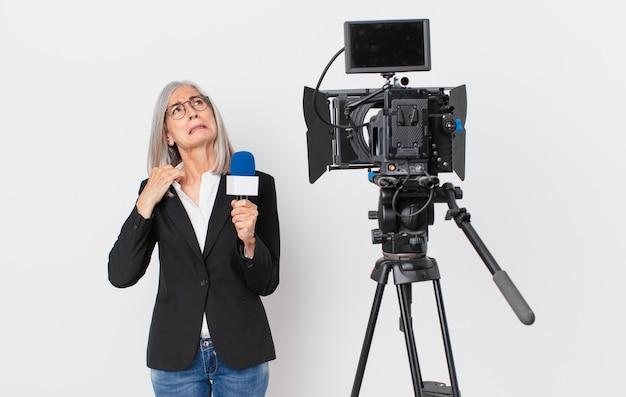 Witte haarvrouw van middelbare leeftijd die zich gestrest, angstig, moe en gefrustreerd voelt en een microfoon vasthoudt. tv-presentator concept
