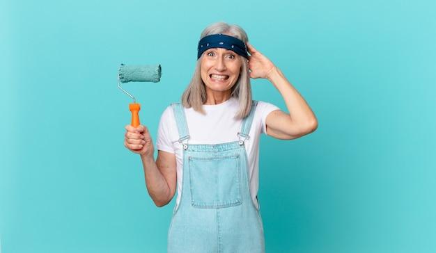 Witte haarvrouw van middelbare leeftijd die zich gestrest, angstig of bang voelt, met de handen op het hoofd met een roller die een muur schildert