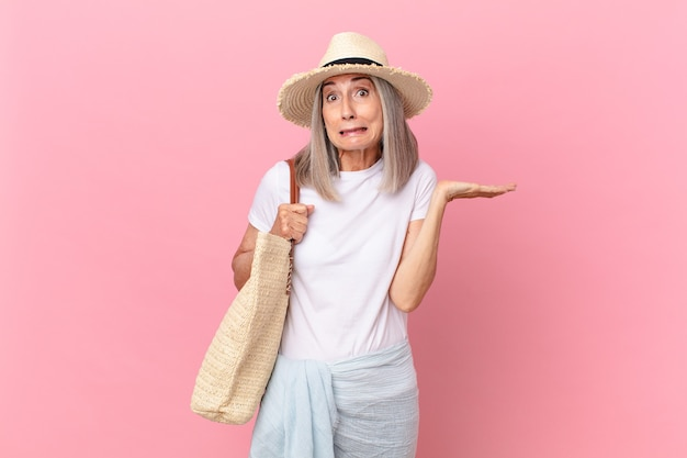Witte haarvrouw van middelbare leeftijd die zich verbaasd en verward en twijfelend voelt. zomer concept