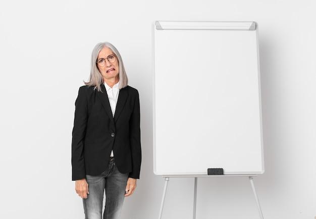 Witte haarvrouw van middelbare leeftijd die zich verbaasd en verward voelt en een bord kopieerruimte. bedrijfsconcept