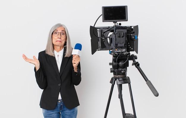 Witte haarvrouw van middelbare leeftijd die zich verbaasd en verward voelt en twijfelt en een microfoon vasthoudt. tv-presentator concept
