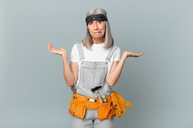 Witte haarvrouw van middelbare leeftijd die zich verbaasd en verward voelt en twijfelt en werkkleding en gereedschap draagt. huishoudconcept