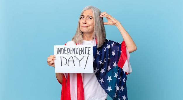 Witte haarvrouw van middelbare leeftijd die zich verbaasd en verward voelt, hoofd krabben. onafhankelijkheidsdag concept