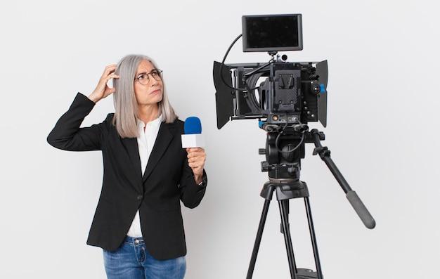 Witte haarvrouw van middelbare leeftijd die zich verbaasd en verward voelt, hoofd krabt en een microfoon vasthoudt. tv-presentator concept